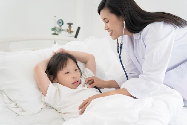 Bambina pediatrica degli esami di medico con lo stetoscopio