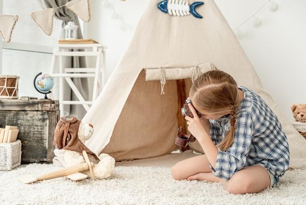 Bambina piacevole che fotografa l'orsacchiotto della peluche
