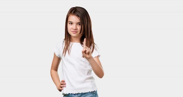 Bambina piena del corpo che mostra numero uno, simbolo del conteggio, concetto di matematica