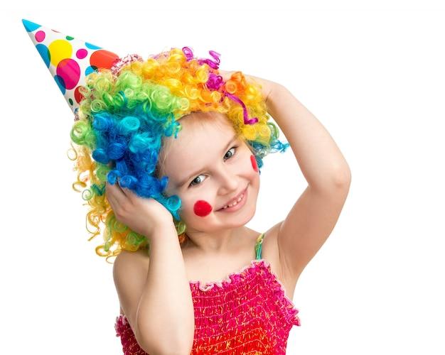 Bambina positiva che posa nella parrucca variopinta del pagliaccio isolata su fondo bianco