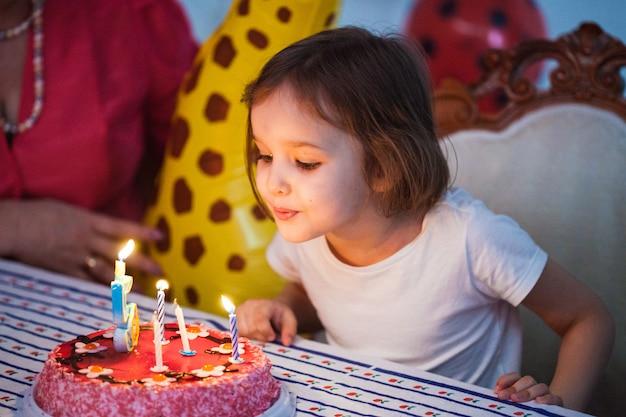 Bambina, ragazza di compleanno che spegne le candele sulla torta, celebrazione di compleanno con gli amici