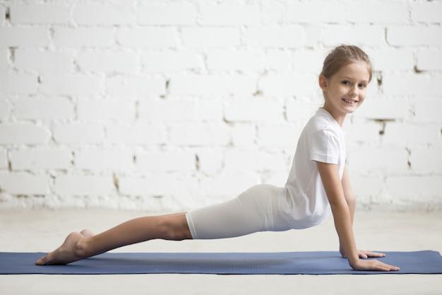 Bambina ragazza in posa rivolta verso l'alto, sfondo bianco studio