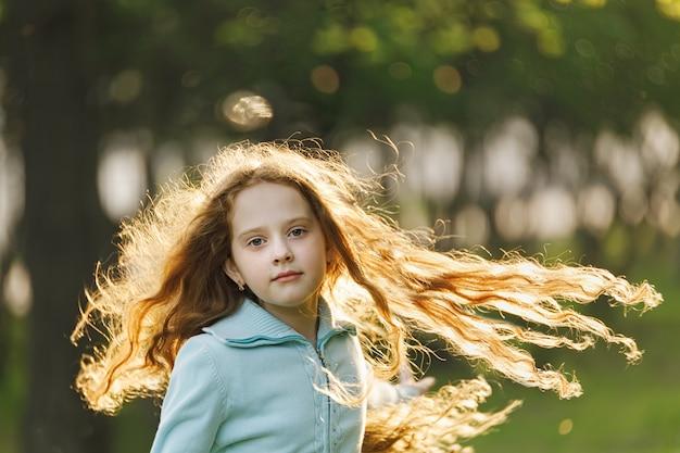Bambina riccia con capelli rossi volanti.
