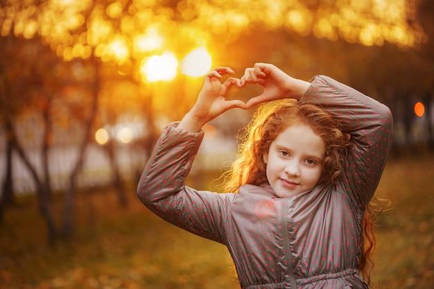Bambina ridendo nel parco d'autunno. sano, concetto di stile di vita.
