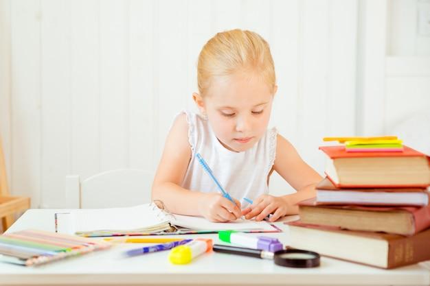 Bambina scrivendo qualcosa nel quaderno e seduto al tavolo.