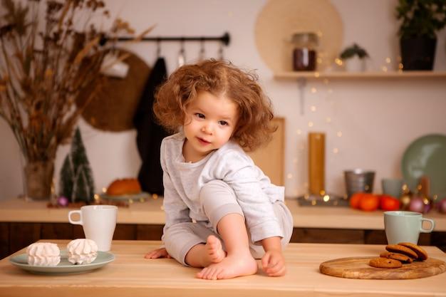 Bambina seduta nella cucina di natale sul tavolo