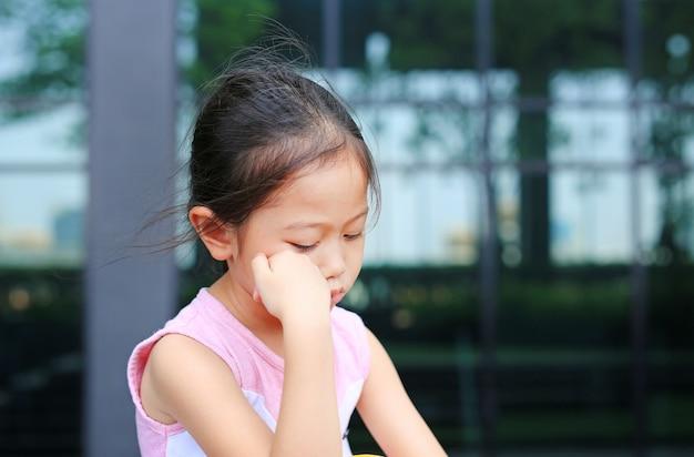 Bambina seria con postura la mano sulla guancia