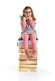 Bambina sorpresa con gli occhiali che si siedono sui libri. di nuovo a scuola