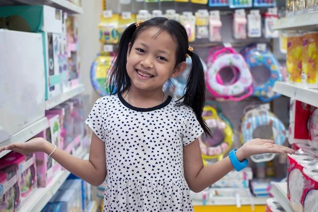 Bambina sorridente asiatica in negozio