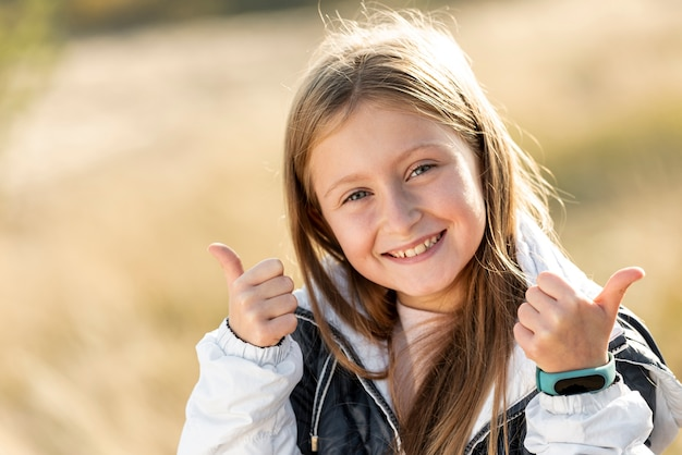 Bambina sorridente che mostra segno giusto