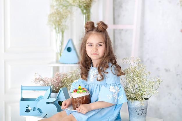 Bambina sorridente che si siede alla tavola bianca in cucina con il panettone di pasqua. interno di pasqua. decorazioni per la casa di primavera. famiglia felice si prepara per la pasqua. torta di pasqua in mano della bambina. coniglietto, uova