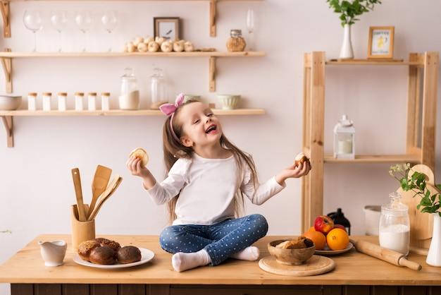 Bambina sorridente che si siede sulla superficie di lavoro della cucina in attesa di colazione. ragazza allegra e birichina in cucina.
