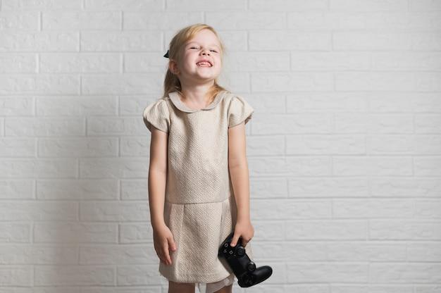 Bambina sorridente che tiene un controller