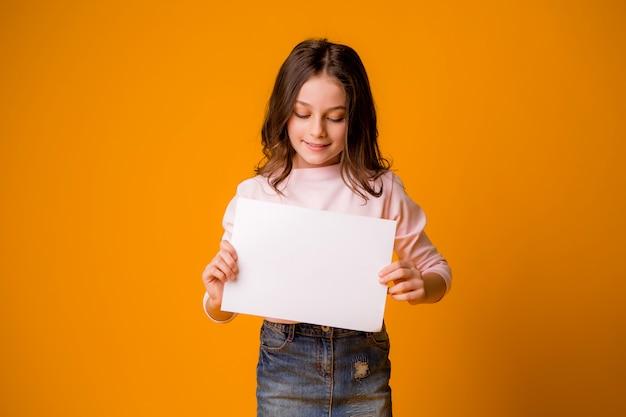 Bambina sorridente con un foglio bianco su uno sfondo giallo