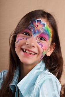 Bambina sorridente divertente felice con la pittura del fronte