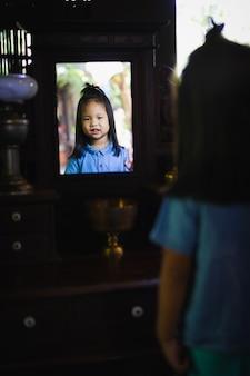Bambina sorridente e guardarsi allo specchio