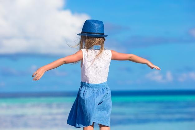 Bambina sorridente felice adorabile in cappello sulla vacanza della spiaggia