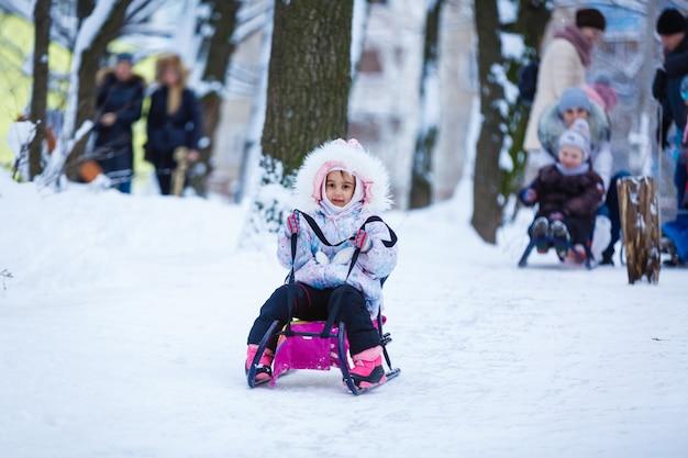 Bambina sorridente graziosa nella sua tuta da sci che scivola giù da una piccola collina innevata