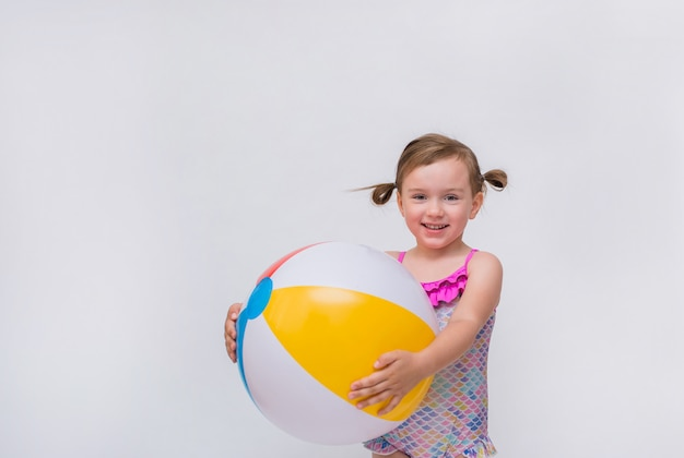 Bambina sorridente in un costume da bagno con una palla gonfiabile su un bianco isolato