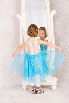 Bambina sorridente in vestito blu che osserva specchio.
