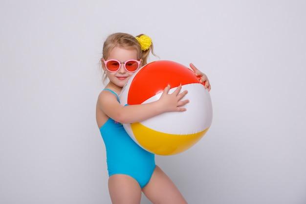 Bambina sorridente sveglia in costume da bagno con l'anello di gomma isolato su bianco