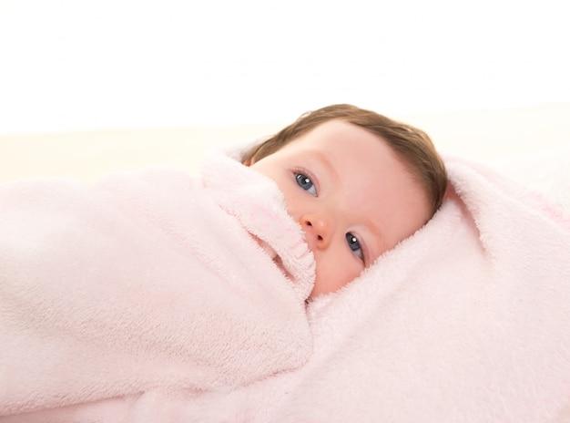 Bambina sotto coperta rosa nascosta su pelliccia bianca