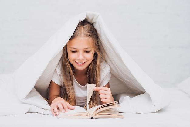 Bambina sotto la coperta che legge un libro