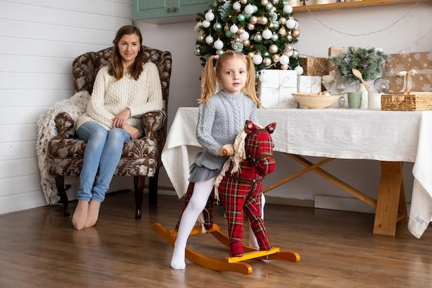 Bambina sul cavallo giocattolo nella cucina di natale a casa.