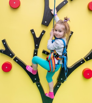 Bambina sulla parete da arrampicata per bambini