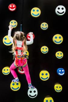 Bambina sulla parete di arrampicata per bambini