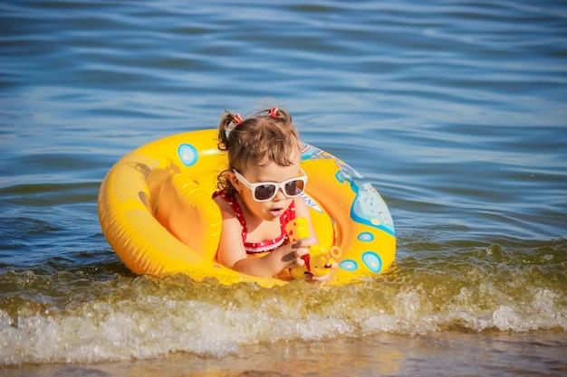 Bambina sulla spiaggia, in riva al mare. messa a fuoco selettiva