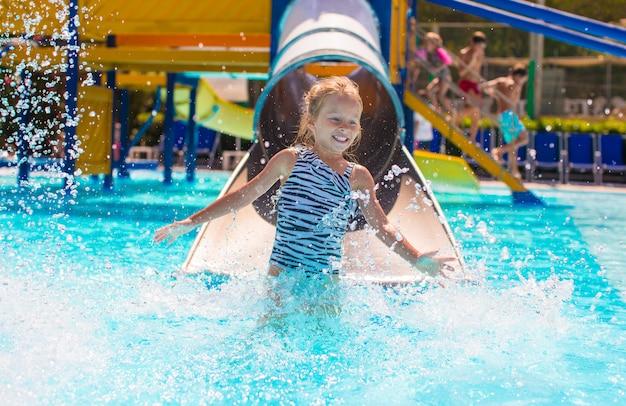 Bambina sullo scivolo d'acqua a aquapark in vacanza estiva