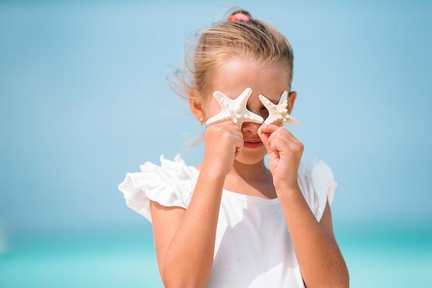 Bambina sveglia alla spiaggia durante le vacanze estive