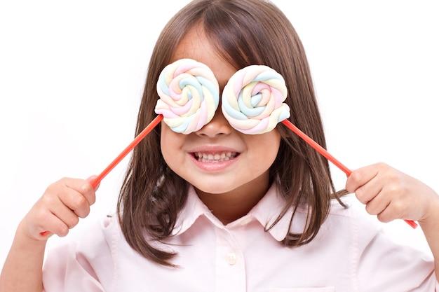 Bambina sveglia allegra che posa con la caramella gommosa e molle dolce di colore pastello
