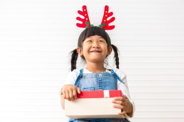 Bambina sveglia allegra di natale e di feste felici che tengono il contenitore di regalo attuale al salone bianco.