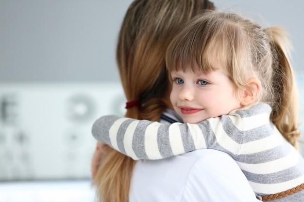 Bambina sveglia che abbraccia medico femminile nel suo ufficio