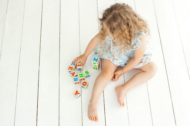 Bambina sveglia che gioca con i cubi di abc. bambino che studia a sfondo neutro