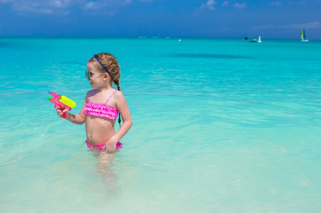 Bambina sveglia che gioca con i giocattoli durante la vacanza caraibica
