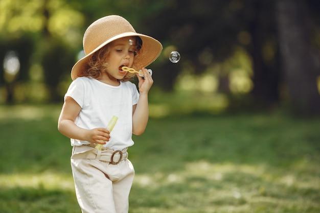 Bambina sveglia che gioca in un parco estivo