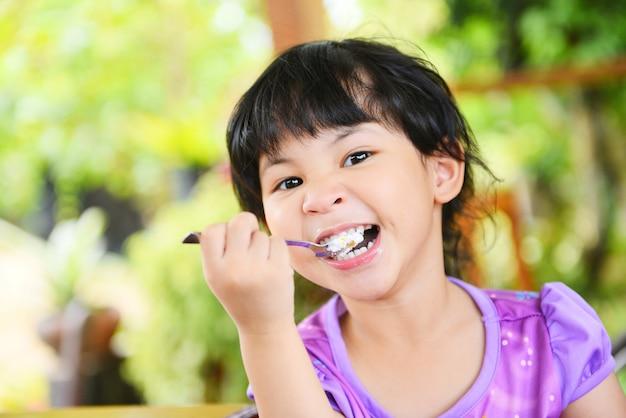 Bambina sveglia che mangia torta. bambino asiatico felice e che tiene un cucchiaio nella bocca con il dolce sul tavolo da pranzo, fuoco selettivo