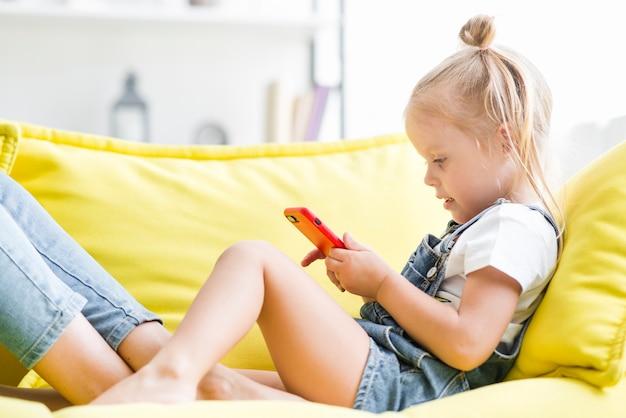 Bambina sveglia che per mezzo del telefono cellulare