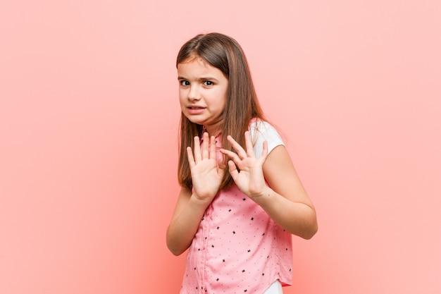 Bambina sveglia che rifiuta qualcuno che mostra un gesto di disgusto