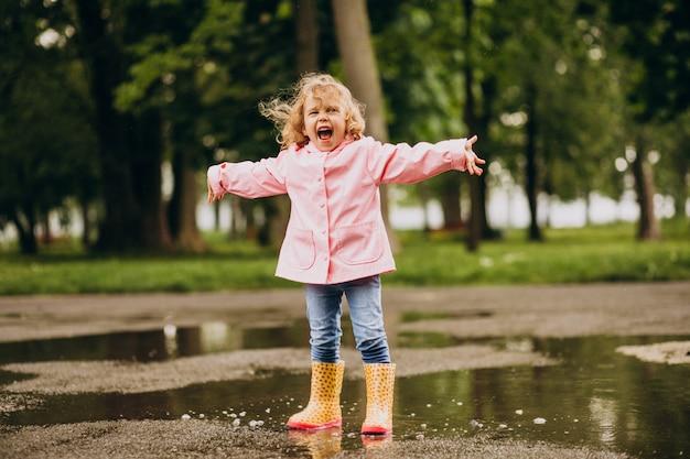 Bambina sveglia che salta nella pozza in un tempo piovoso