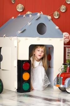 Bambina sveglia che si nasconde in una casa di cartone e che gioca con un grande autopompa antincendio del giocattolo
