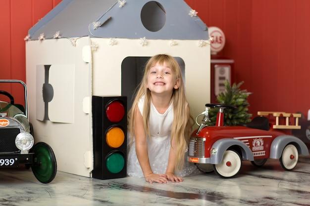 Bambina sveglia che si nasconde in una casa di cartone e che gioca con un grande autopompa antincendio del giocattolo.