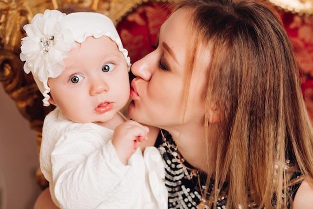 Bambina sveglia che si siede con la madre. periodo natalizio.