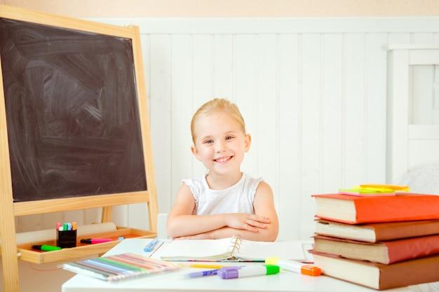 Bambina sveglia che si siede dalla tavola con i pastelli e quaderno aperto davanti a lei