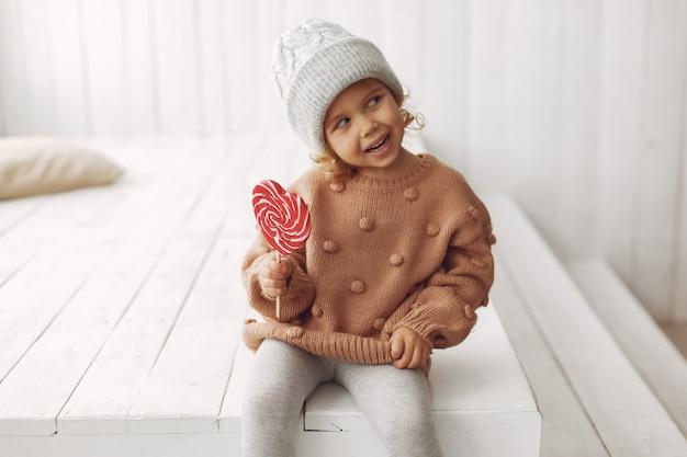 Bambina sveglia che si siede e che mangia caramella