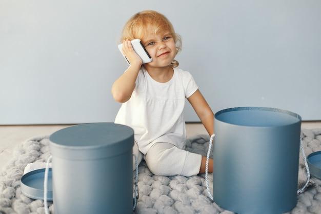 Bambina sveglia che si siede in uno studio con la scatola dei presente