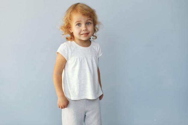 Bambina sveglia che si siede in uno studio su una priorità bassa blu